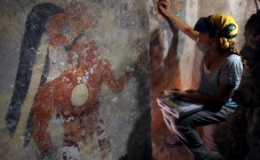 Conservator Angelyn Bass cleans and stabilises the surface of a wall of a Maya house that date to the 9th century. The figure of a man who may have been the town scribe appears on the wall to her left. Image: Tyrone Turner/2012 National Geographic